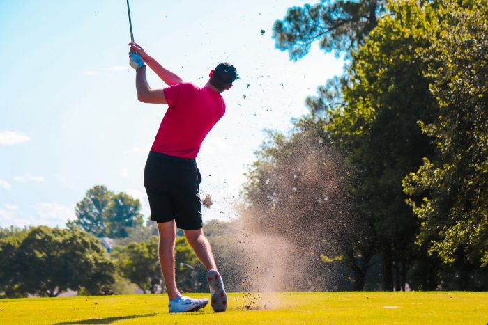 Man playing golf in red t-shirt